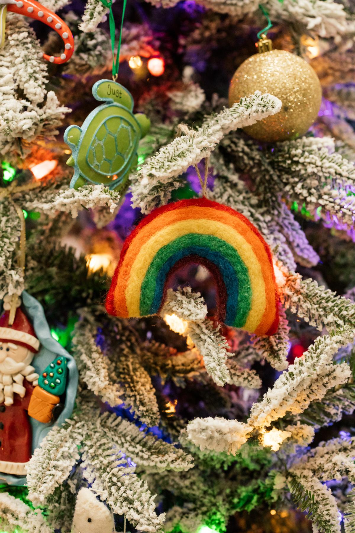 Indoor Holiday decor of lit Christmas tree and felt rainbow ornament