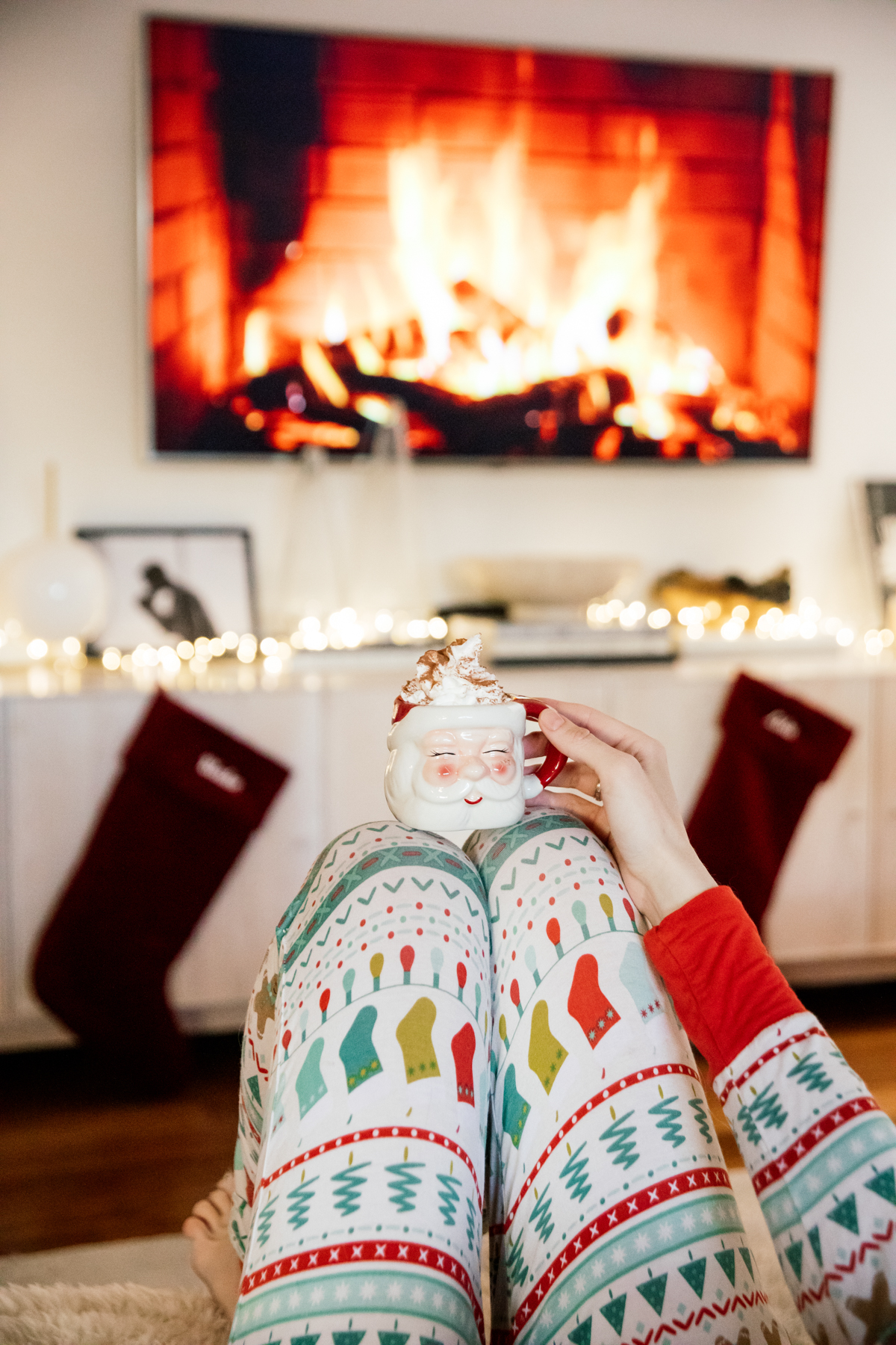 Indoor Holiday decor of twinkle lights tree, twinkle lights, clear glass Christmas tree cloche, and custom embroidered stockings and santa clause mug with hot chocolate