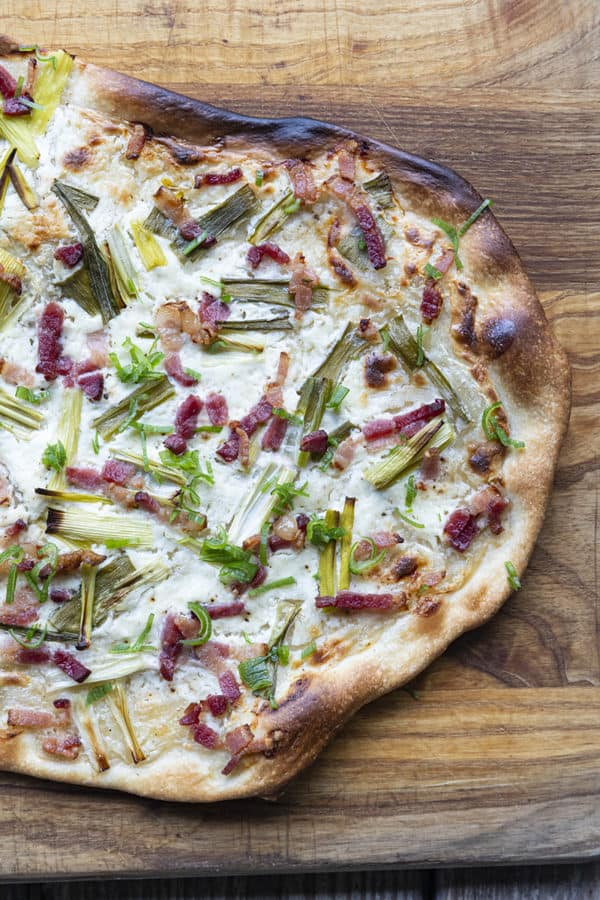 Flammekueche, tarte Flambée, or flammkuchen is a fast and easy bacon and onion pizza type flatbread made with crème fraîche or sour cream. No yeast needed!